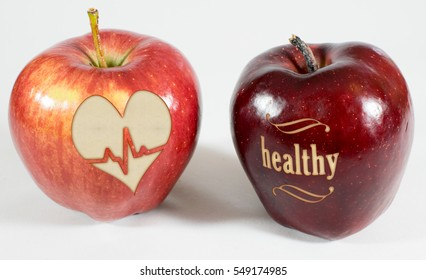 2 red apples on a white background, 1 Apple bears the inscription healthy the other a heart with heartbeat