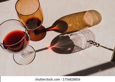 2 red wine glasses with long shadows, rainbow light with wine opener