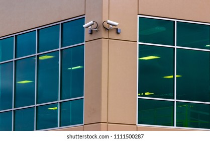 2 security cameras on the side of a building with windows and a sensor