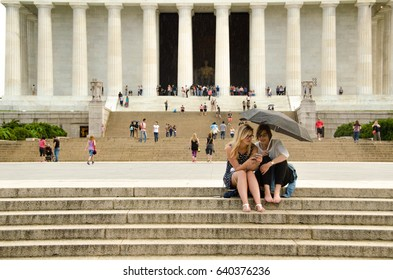 2 SEPT 2016 Two women are sitting on the stairs behind the Lincoln monument under the rain. Looking at the phone with an umbrella in the hand in Washington dc. USA