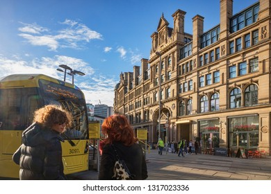 2 September 2018: Manchester, UK - Exchange Square, with Corn Exchange building, Metrolink tram, two young women with backlit hair, and flare.