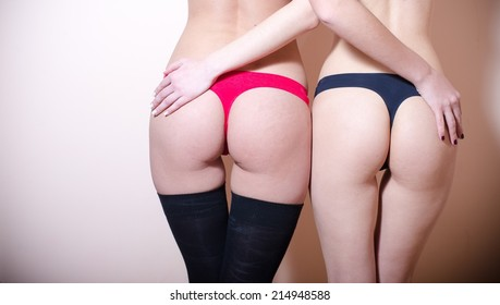 2 super sexy young pretty ladies with perfect buttocks having fun hugging and posing back to camera on light copy space background