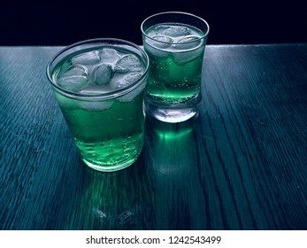 2 sweet refreshing cold cocktail drinks with lots ice and bubbles.  Both drinks have a green color and contain alcohol. These drinks are standing in a cold environment. There is a black background.