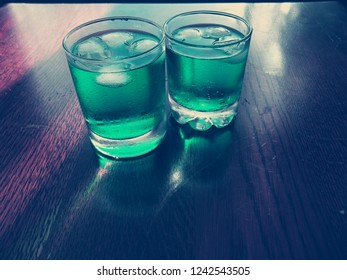 2 sweet refreshing cold cocktail drinks with a green color and ice.  Both drinks contain alcohol. Some bubbles can be seen. There are water drops on the glass. There is condensation on the glass.