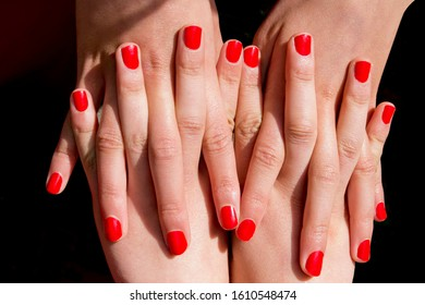 2 teenagers intertwine their fingers which are tipped with bright red nails