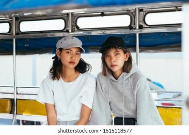 2 Thai girls sitting in baht bus during their trip on summer.