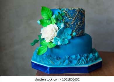 2 Tier blue birthday or wedding cake with gold embroidery and sugar flowers