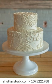 2 tier wedding cake with butter cream frosting and lace piping design.