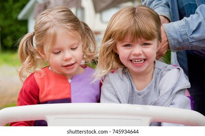 2 toddler Caucasian girls age 2 are playing outside in a toy car.
