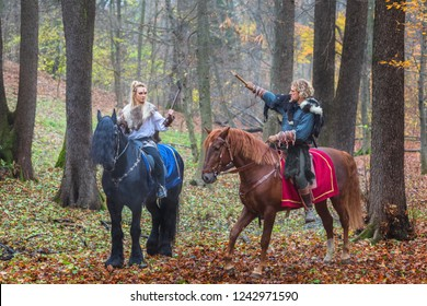 2 (two) dangerous scandinavian viking warriors riding horses and raising axes above head in forest. Northern warriors Vikings ready to raid