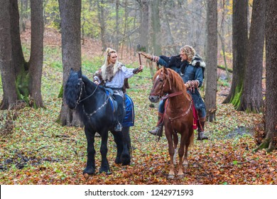 2 (two) dangerous scandinavian viking warriors riding horses and raising axes above head in forest, ready to battle. Northern warriors Vikings ready to raid