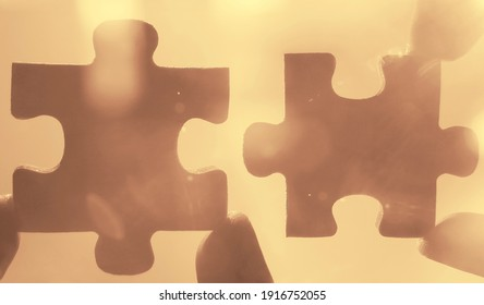 2 two fingers trying to connect puzzle piece. sunny sky background. Jigsaw wooden puzzles on sun rays. one part of the whole. symbol of association and connection.business strategy.