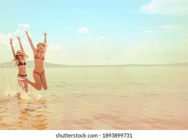2 two Girls  jumping high with arms up spectacular sunrise at ocean coast.