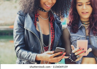 2 urban girls using cell phones hanging out outdoors. fashionable best friends having fun with smartphones. concept of modern multi-ethnic youth and communication technology. midsection crop.