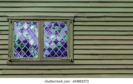 2 vintage windows with purple panes in a leaded diamond pattern on a colonial building with copy space