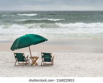 2 Vintage wood and canvas beach lounge chairs and umbrella on deserted stormy beach. Selective focus, artistic blurs.