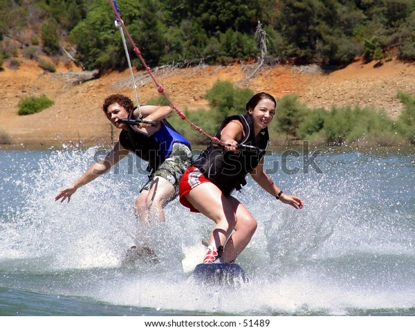 2 wakeboarders behind the boat