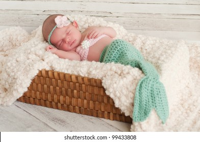 2 week old newborn girl wearing a crocheted mermaid costume, sleeping in a basket with a bleached wood background.