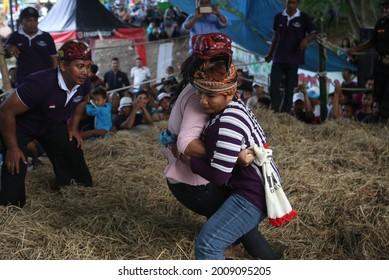 "2 women doing ""Gulat Okol"" while celebrating harvest season, in Surabaya 31 March 2018"