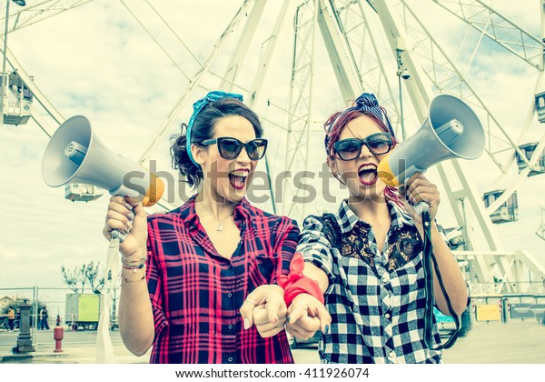 2 women shouting with megaphones - female activists march at a student strike protest rally - workers day or political demonstration - concept of rebel women in street protests for rights activism