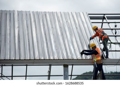 2 workers for construction, installing metal roofing tools, sheet metal New electric drill tool used on a new roof with metal sheets.