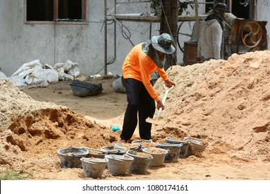 2 workers at the construction site  with a shovel and many buckets of sand