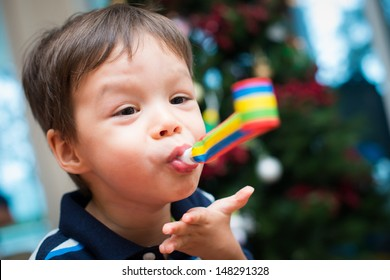2 year old Asian Caucasian boy celebrates Christmas with a party blower and a Christmas tree in background