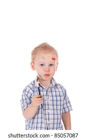 2 year old boy covered in paint. Holding brush, over white