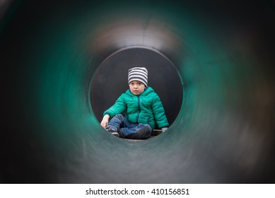 2 year old boy having fun outdoors on playground