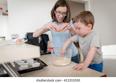 2 year old boy having fun preparing dough for muffins with mother in kitchen at home