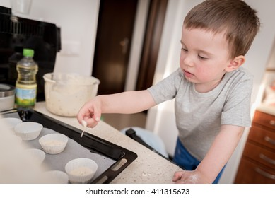 2 year old boy having fun preparing dough for muffins in kitchen at home