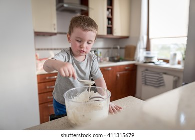 2 year old boy having fun preparing dough for muffins with chocolate chips in kitchen at home