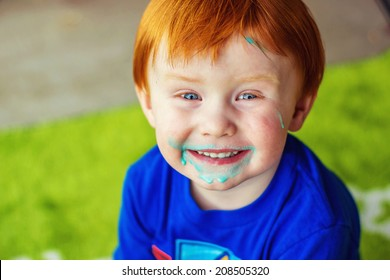 2 year old boy sitting on his patio with blue ice cream all over his face -- image taken in Reno, Nevada, USA