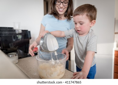 2 year old boy standing on chair in kitchen with his mother and preparing dough for chocolate chip cookies with food processor
