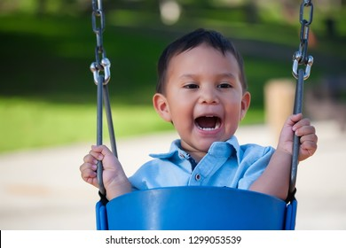 2 year old boy yelling out loud while riding a blue swing at a local park.
