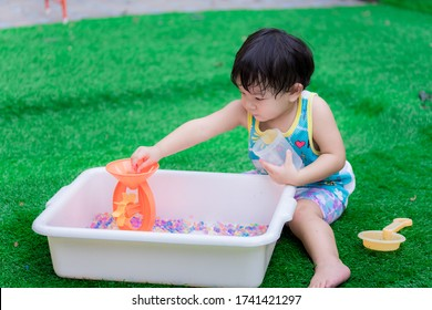 2 year old child boy is playing colorful water beads in white basin. Kid picks up rainbow beads on orange water wheel to make blades rotate. Concept of sensory learning and practice.