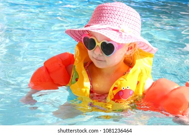 A 2 year old little toddler girl is swimming the pool with arm floaties and a safety life vest on a sunny summer vacation day.