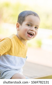 2 year old mixed race asian caucasian boy playing outside in his suburban backyard