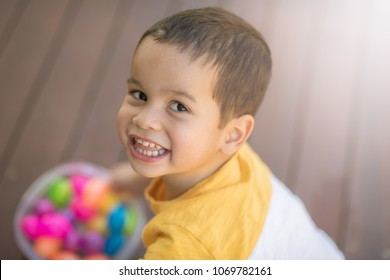 2 year old mixed race asian caucasian boy playing with colorful candy eggs outside on wooden deck