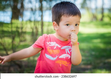 2 year old mixed race Asian Caucasian boy. A cute multicultural Australian boy sucking his thumb playing outside in the summer sun.