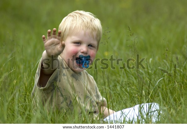 A 2 year old sitting in the grass waving at you.