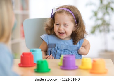 2 year-old child playing with educational cup toys at home