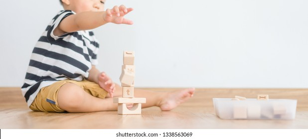 2 years baby boy.Little child boy playing with lots of wooden toys block with mother.Kids play with educational toys at home.Day care and Kindergarten school.child development concept.