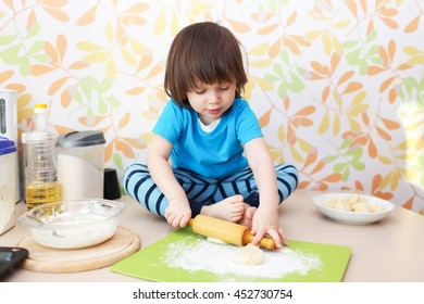 2 years boy flattening dough sitting on a table at home kitchen