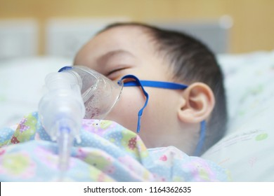 2 years old Asian toddler boy has asthma or pneumonia disease and need nebulizations,Sick boy rest on patien bed and has inhalation therapy by the mask of inhaler.Sick or cancer child awareness.