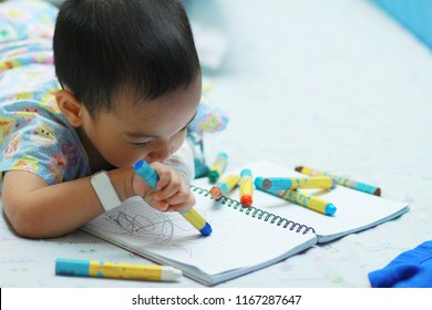 2 years old Asian toddler boy painting or drawing by using color pencil at the hospital,Sick boy rest on patien bed in patient suit relax by painted on the sketch book.Sick or cancer child awareness.