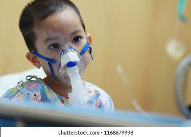 2 years old Asian toddler boy has asthma or pneumonia disease and need nebulizations,Sick boy rest on patient bed and has inhalation therapy by the mask of inhaler.Sick or cancer child awareness.