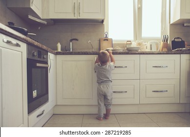 2 years old child standing on the floor alone in the kitchen, casual lifestyle photo series in real life interior