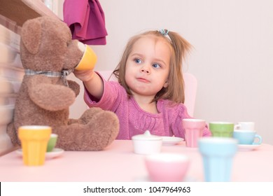 2 years old girl playing tea party with a teddy bear