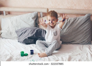 2 years old little boy dressed in pajamas is painting in the bed